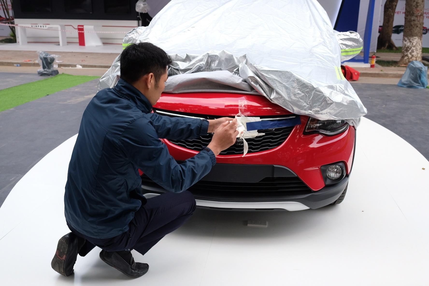 Một nhân viên của hãng đang tháo bỏ lớp bảo vệ logo VinFast phía đầu xe trên chiếc Fadil