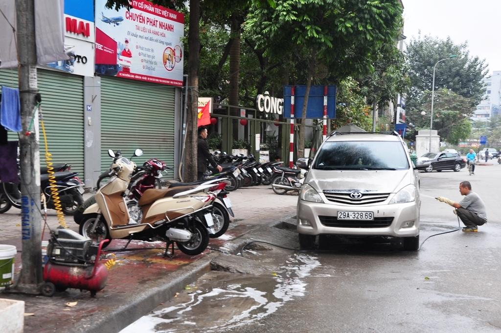 Hộ tư nhân trên đường Láng ngày thường sửa chữa xe máy, nhưng ngày Tết cũng tham gia rửa cả ô tô để kiếm thêm thu nhập.