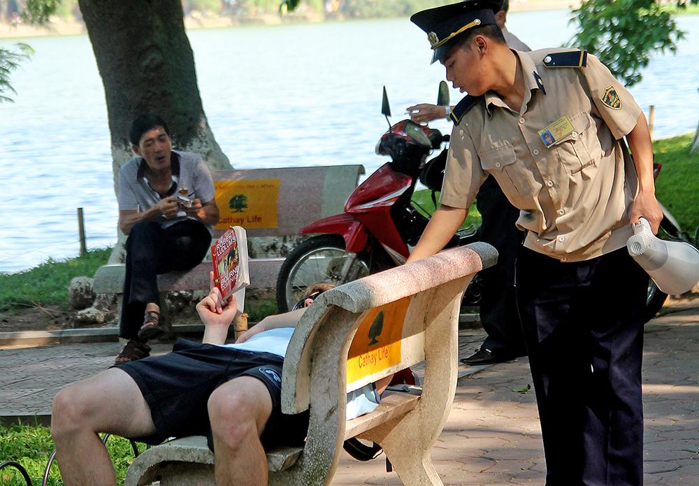 Dù miễn cưỡng nhưng nhân viên trật tự vẫn nhắc nhở du khách nước ngoài không nằm khi tránh nắng quanh khu vực Hồ Gươm