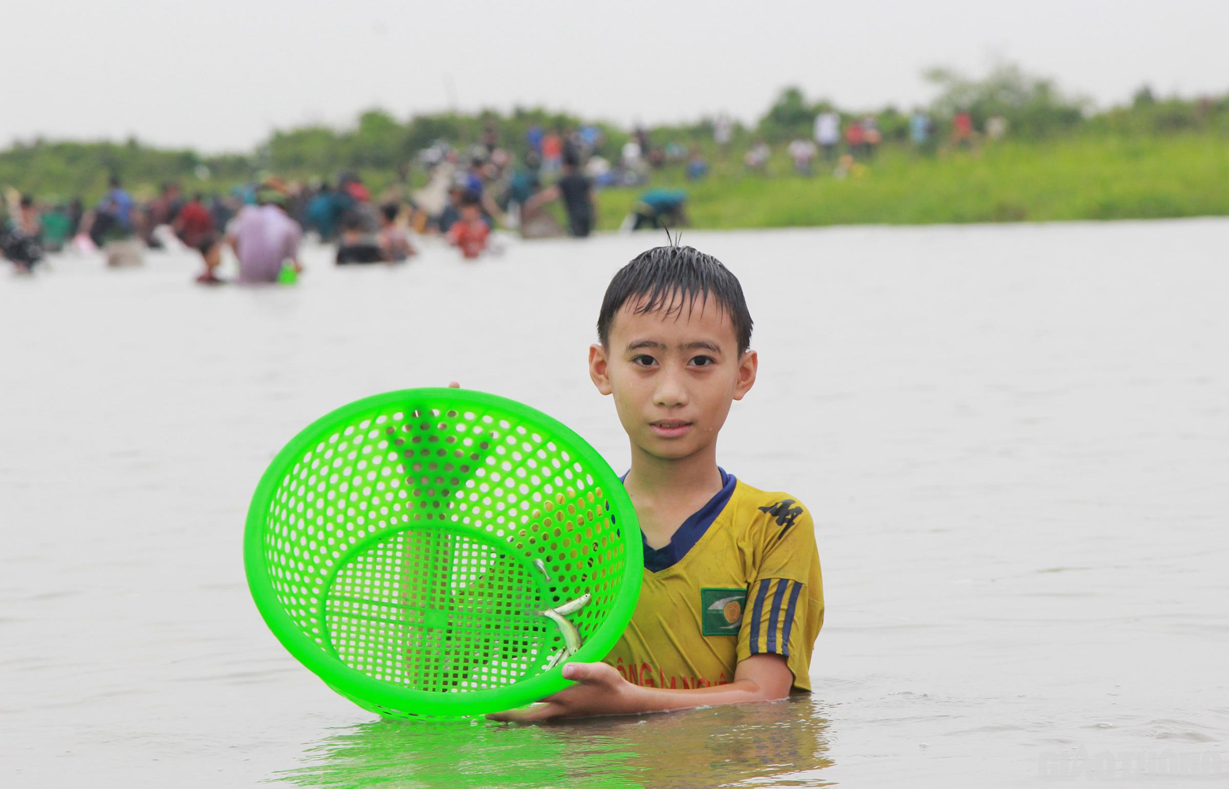 Nhiều cháu bé cũng theo bố mẹ, anh chị xuống đầm bắt cá với hi vọng may mắn sẽ đến với bản thân mình