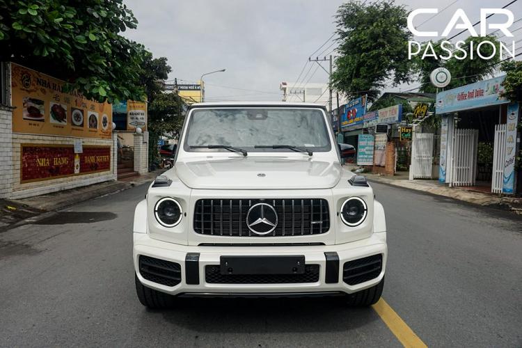 """Tại thị trường Việt Nam, những chiếc Mercedes-Benz G63 2019 mới thường được trang bị lớp sơn tối màu ở phần ngoại thất nhằm phô ra những đường nét thiết kế hầm hố, chỉ có 3 chiếc mang màu trắng xuất hiện trên đường phố cả nước. Trong đó, một chiếc đang định cư tại Hà Nội, một chiếc ở Sài Gòn thuộc sở hữu của doanh nhân Phạm Trần Nhật Minh và chiếc còn lại vừa chính thức """"làm dâu"""" tỉnh Bình Dương"""