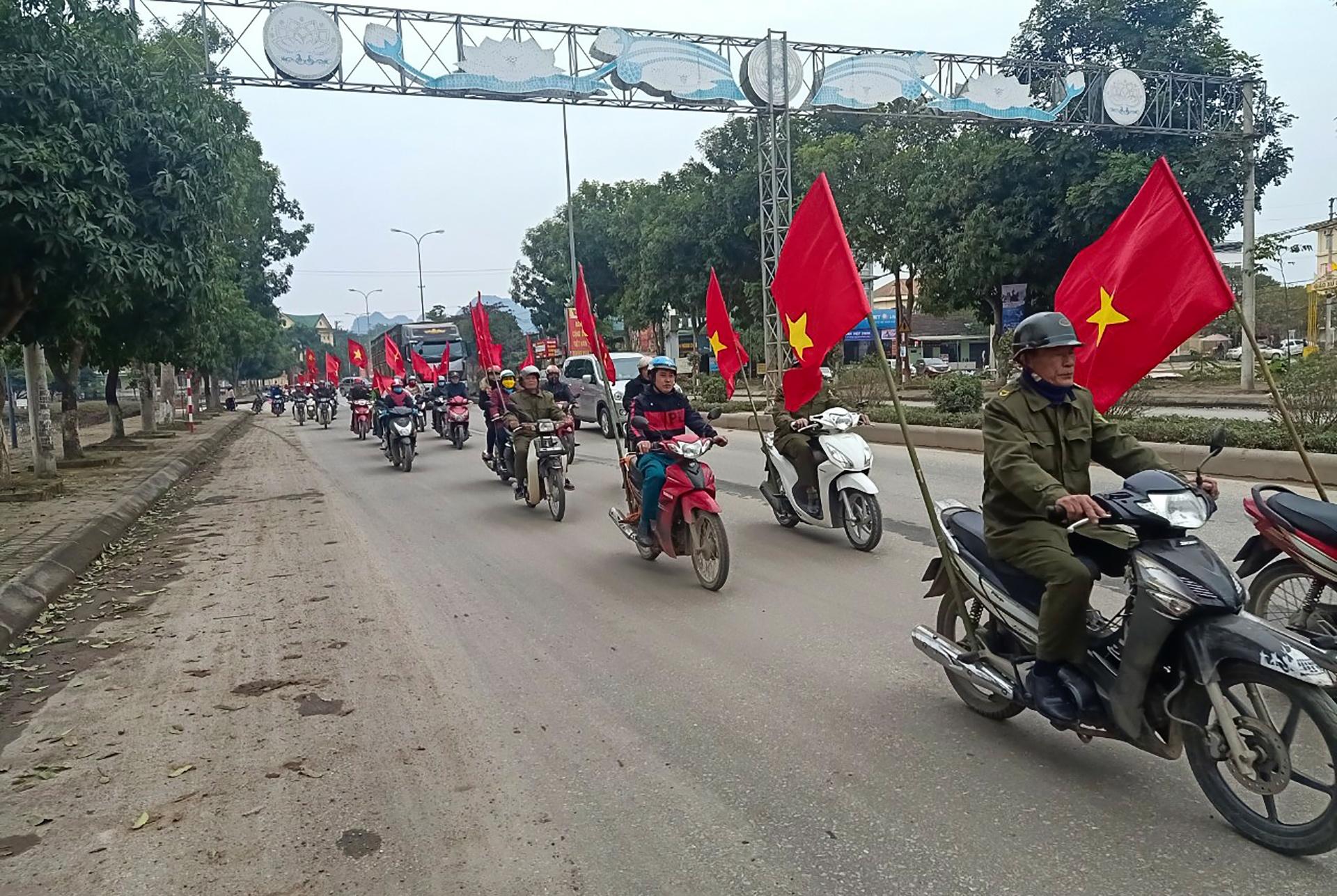 Người dân Anh Sơn mang theo cờ Đảng và cờ Tổ quốc diễu hành trên đường