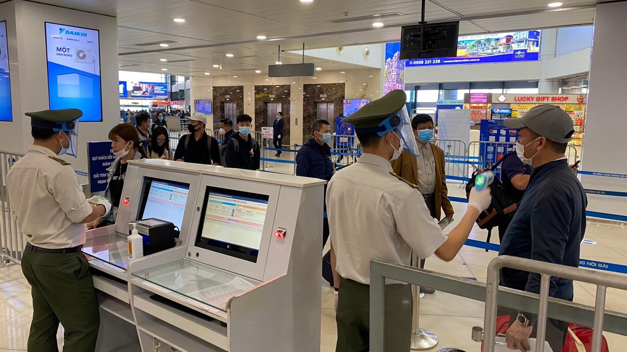 Nhân viên ANHK đo thân nhiệt cho hành khách. Lực lượng An ninh hàng không Nội Bài được trang bị đầy đủ găng tay, khẩu trang, tấm chắn giọt bắn trong khi làm việc.